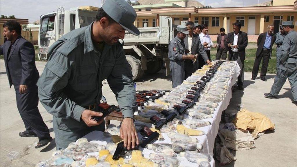 Unos oficiales de los cuerpos de seguridad afganos muestran armas y munición hallados en un vehículo en Pol-e-Khumri, en la provincia de Baghlan, Afganistán, ayer lunes 9 de mayo. EFE