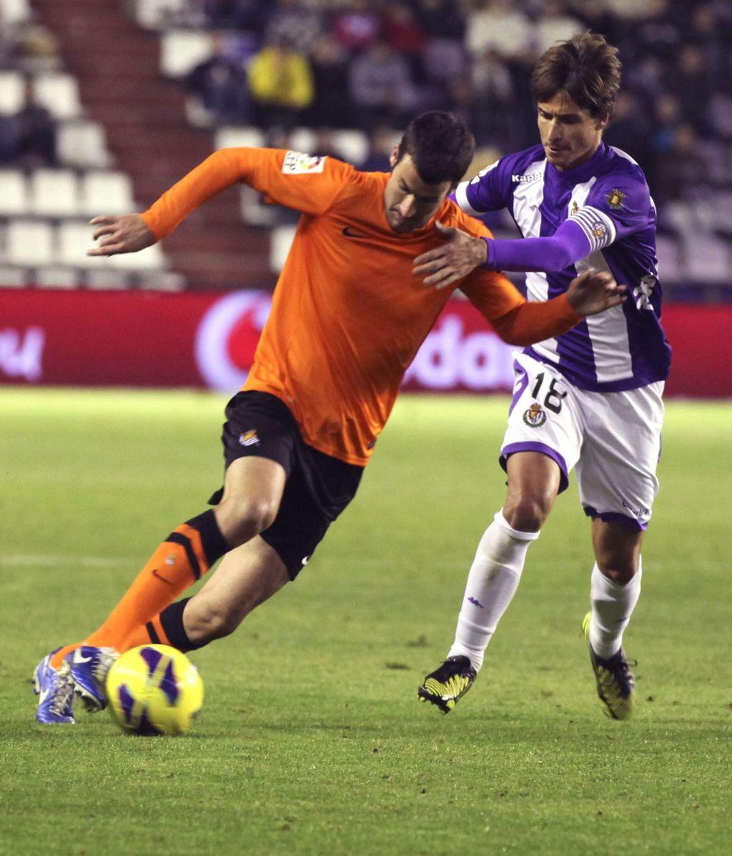 El delantero de la Real Sociedad, Imanol Agirretxe (i), se lleva el balón ante el acoso del defensor del Real Valladolid, Álvaro Rubio