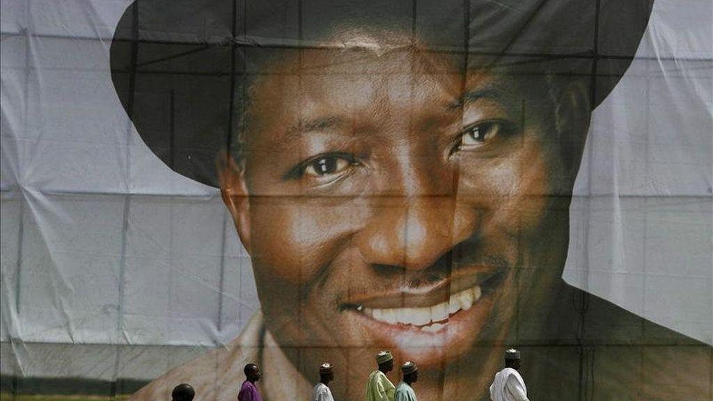 Imagen que muestra a hombres nigerianos que caminan al frente de una pancarta del actual presidente nigeriano, Goodluck Jonathan, durante su campaña electoral, en Kaduna, al noroeste de Nigeria. EFE