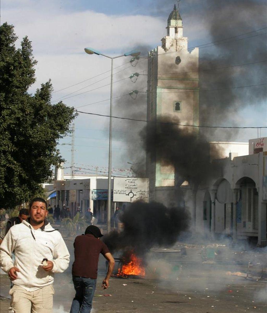 Fotografía de archivo del 10 de enero de 2011 de manifestantes en una barricada incendiada en Regueb (Túnez). EFE/Archivo