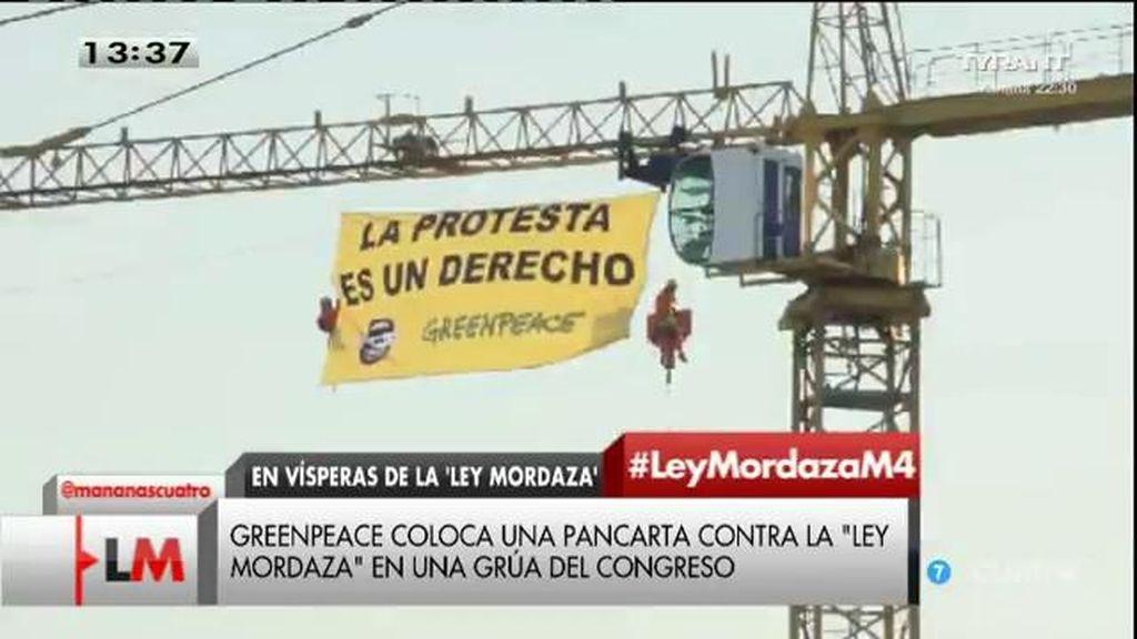 Greenpeace coloca una pancarta contra la 'ley mordaza' en una grúa del Congreso