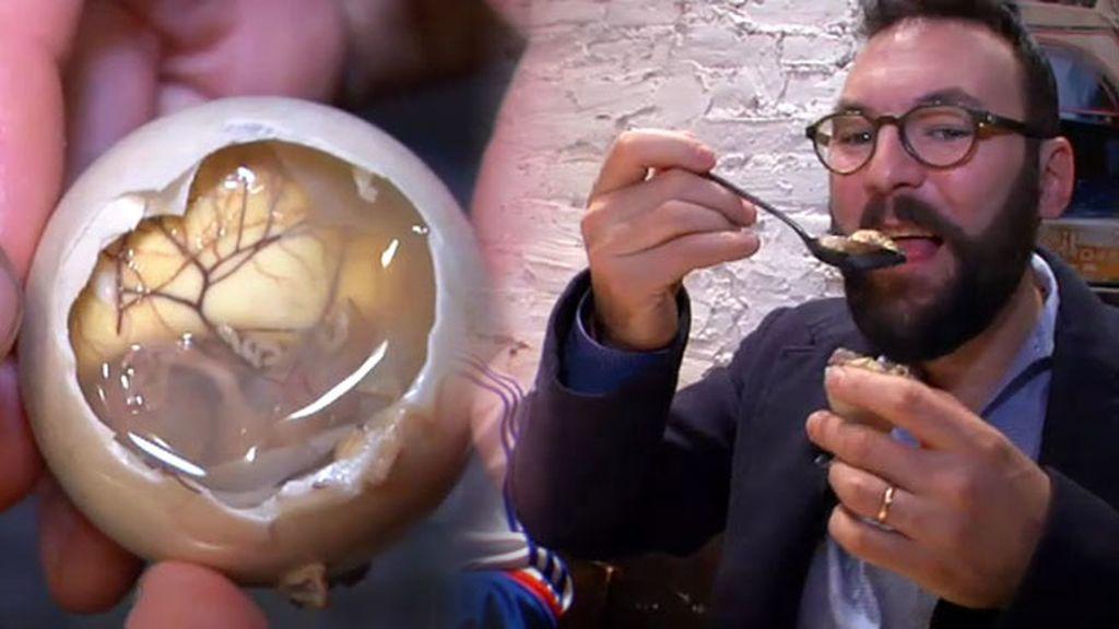 Eder prueba el balut, un huevo de pato cocido que se come con el embrión dentro