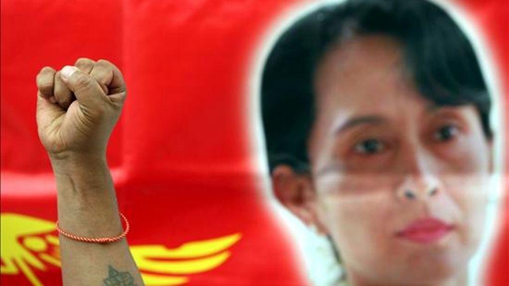 Un manifestante birmano levanta el puño junto a un retrato de la líder opositora birmana Daw Aung San Suu Kyi durante una manifestación en Bangkok (Tailandia) el pasado 19 de junio. EFE/Archivo