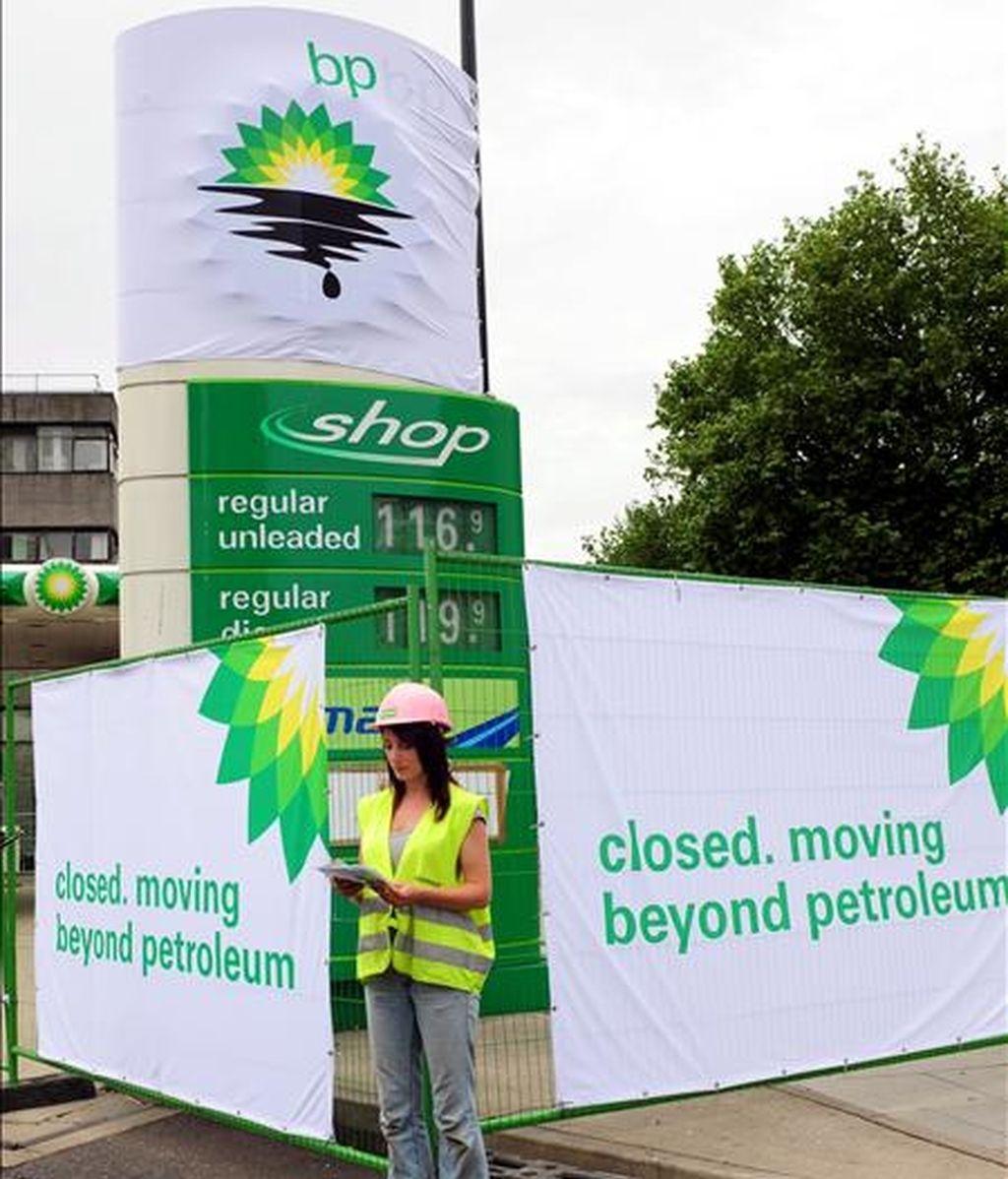 Una activista de la organización ecologista Greenpeace lee un documento junto a una pancarta de denuncia en una estación de servicio de la British Petroleum (BP) en Londres (Reino Unido), hoy, 27 de julio. EFE