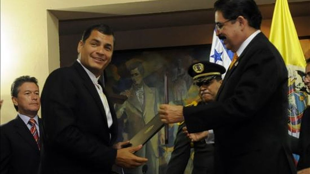 El presidente de Ecuador, Rafael Correa, recibe una condecoración de manos de su homólogo de Honduras, Manuel Zelaya, a su llegada a la casa presidencial en San Pedro Sula (Honduras) durante su visita oficial al país. EFE