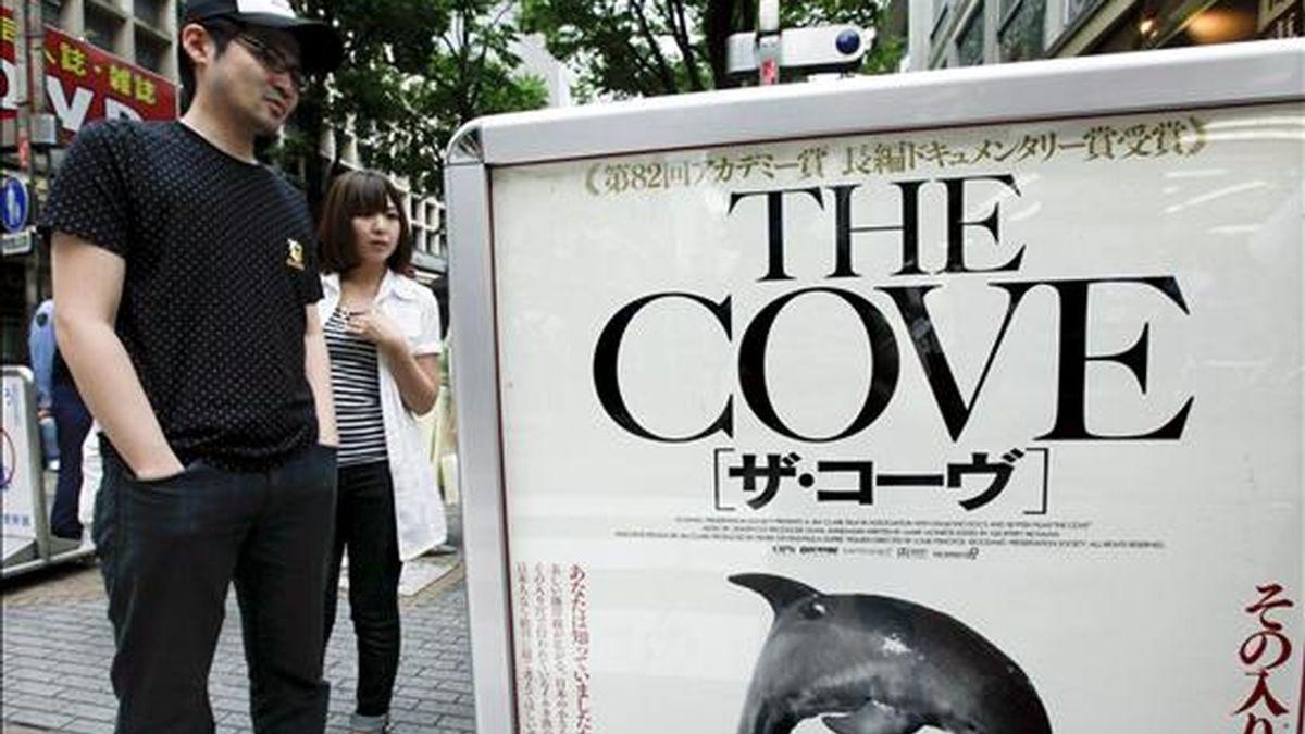 """Un joven observa hoy el cartel promocional del documental """"The Cove"""" colocado a las puertas de un cine de Yokohama (Japón). El documental ganador de un Oscar """"The Cove"""", que explora la sangrienta matanza de delfines en un pueblo de Japón, se estrena hoy en el país asiático en medio de una encendida polémica y las críticas de grupos que lo tachan de anti-japonés. EFE"""