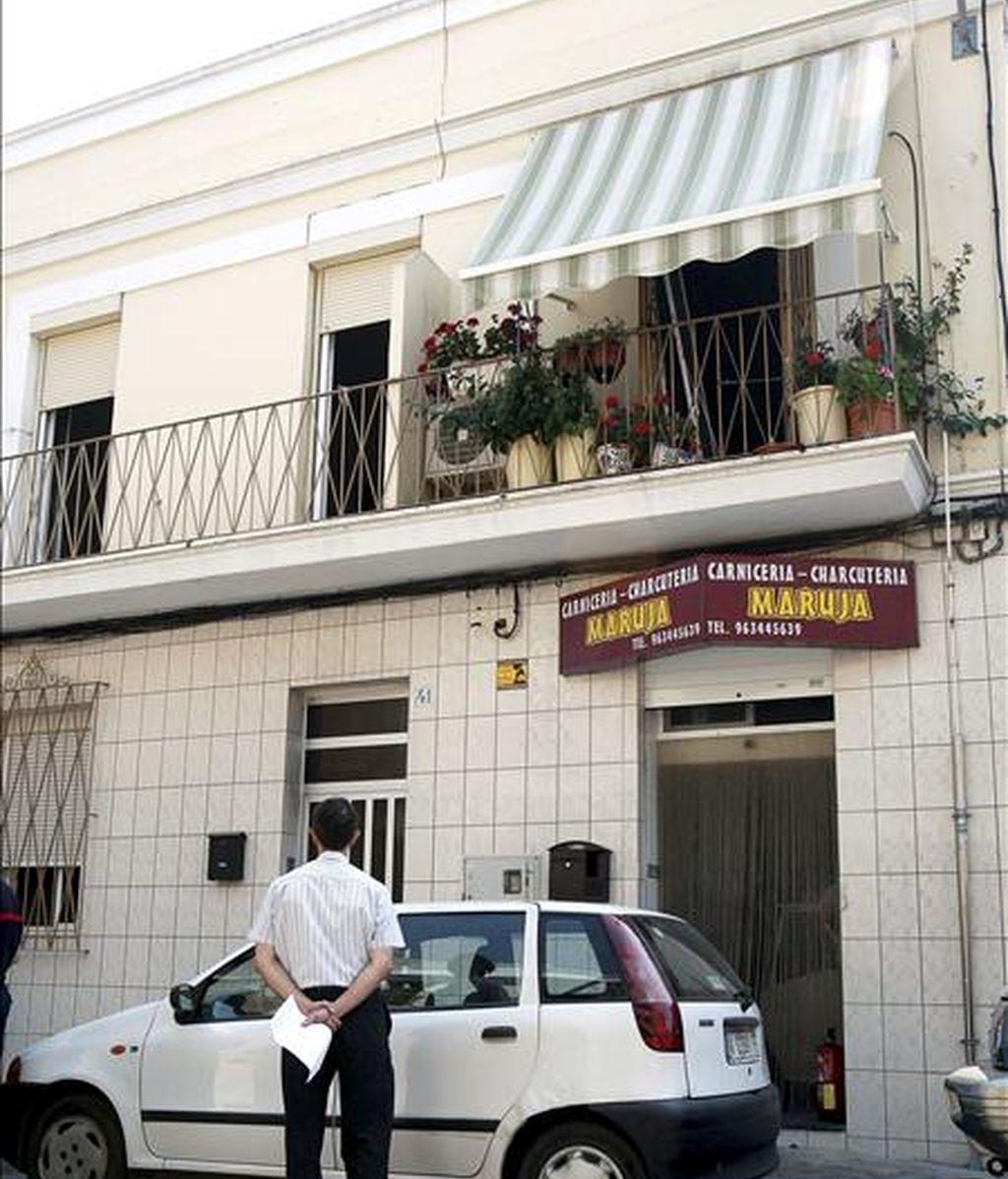 Un trabajador del retén fúnebre observa la vivienda del primer piso en el que ha fallecido una anciana ciega de 84 años en el incendio registrado en su domicilio del barrio del Oliveral de Valencia. EFE