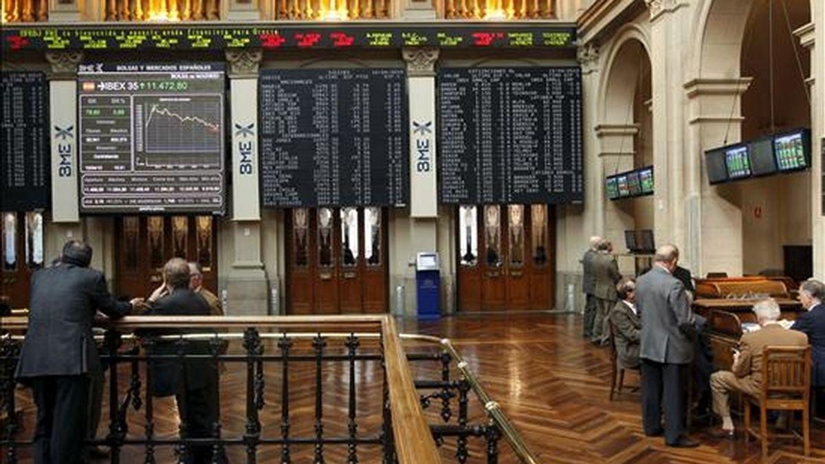 Varios operadores observan el panel del Ibex-35 en la Bolsa de Madrid. EFE/Archivo