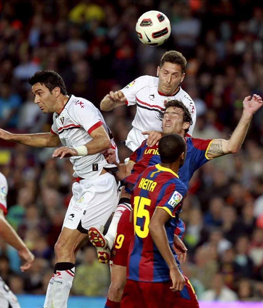 Los jugadores del FC Barcelona Seydou Keita (d-primer término) y Scherrer Maxwell (d-segundo término) pugnan por un balón aéreo con los jugadores de Osasuna Javad Nekounam (i) y Damiá Abellá durante el partido, correspondiente a la trigésima tercera jornad. EFE/Archivo