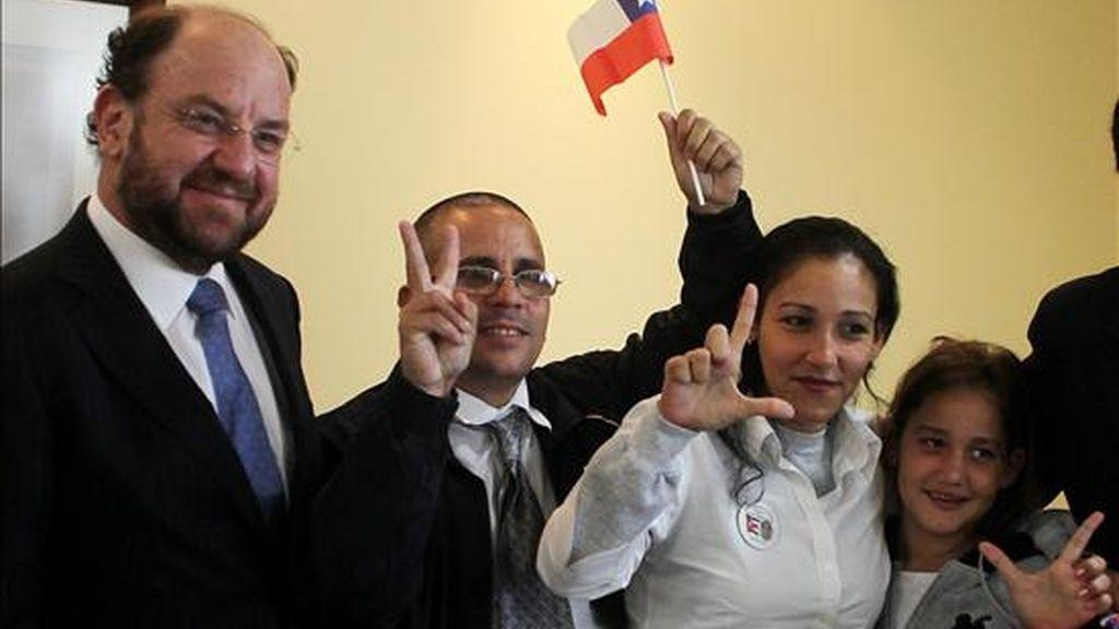 El ministro de Relaciones Exteriores de Chile, Alfredo Moreno (i), el disidente cubano, José Ubaldo Izquierdo (c), y su familia posan para la prensa  durante su arribo al aeropuerto de Santiago (Chile). EFE