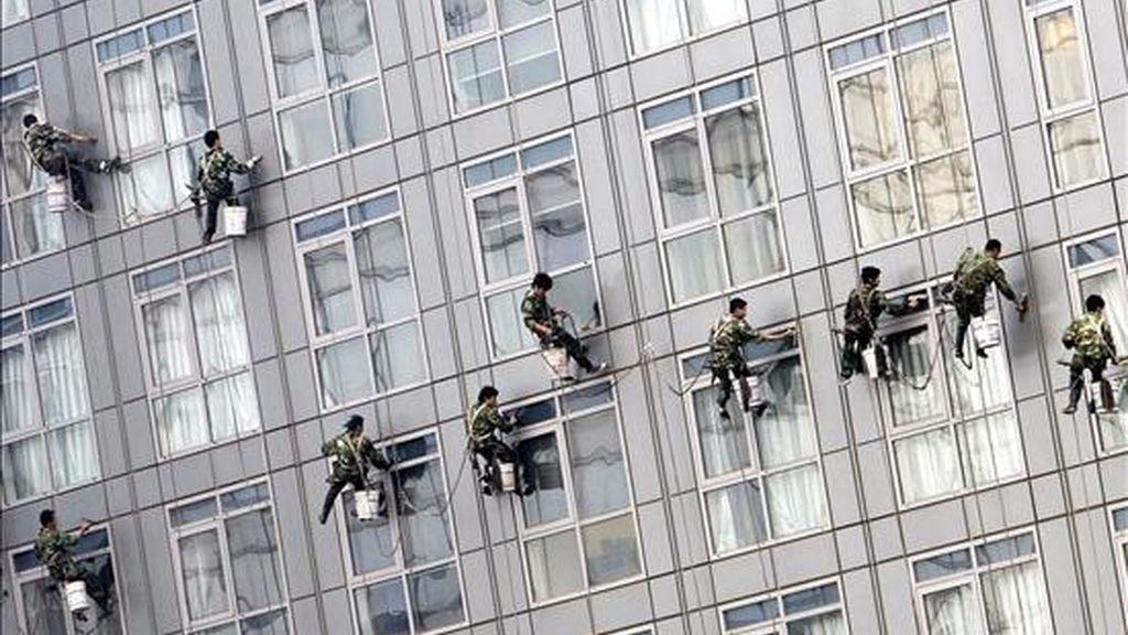 Varios limpiaventanas trabajan en un edificio a las afueras de Pekín. EFE