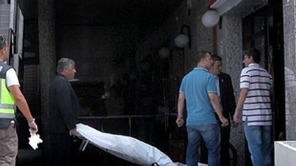 Operarios de los servicios funerarios retiran el cuerpo de una mujer que ha muerto hoy al ser apuñalada en el cuello en un establecimiento de la avenida Juan Carlos I de Arona, al sur de Tenerife. Vídeo: Informativos Telecinco.