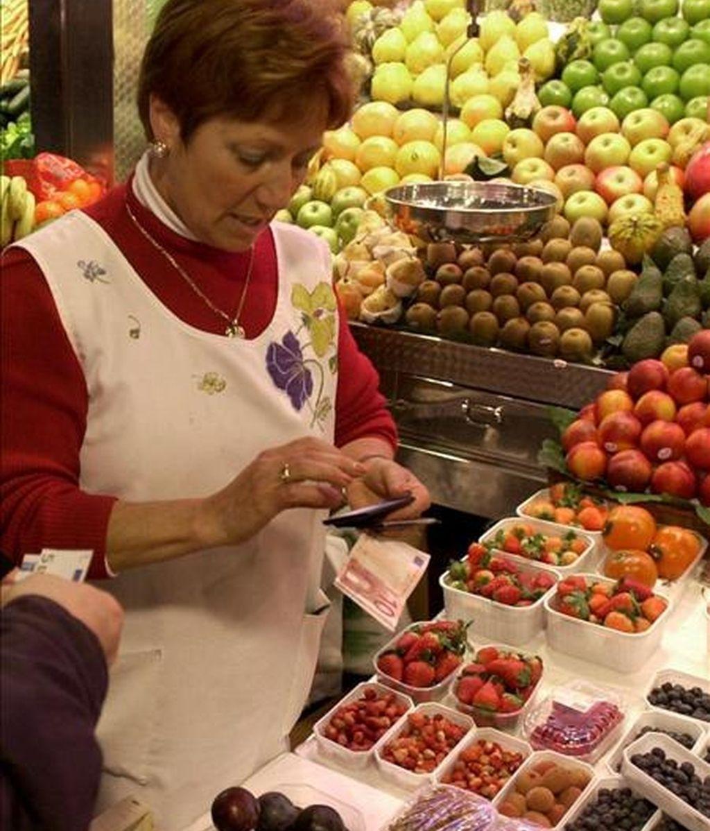 Una dependienta de un puesto de frutas de un mercado. EFE/Archivo