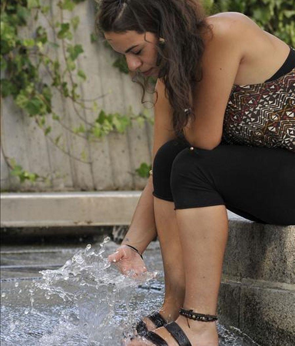 Una joven se refresca el agua de una fuente de la plaza de Tirso de Molina de Madrid, para intentar sofocar las altas temperaturas que se registran en la capital. EFE