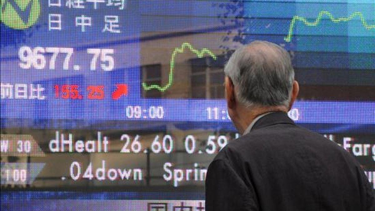 Un hombre contempla la información una pantalla electrónico con el valor del índice Nikkei, en el centro de Tokio. EFE/Archivo