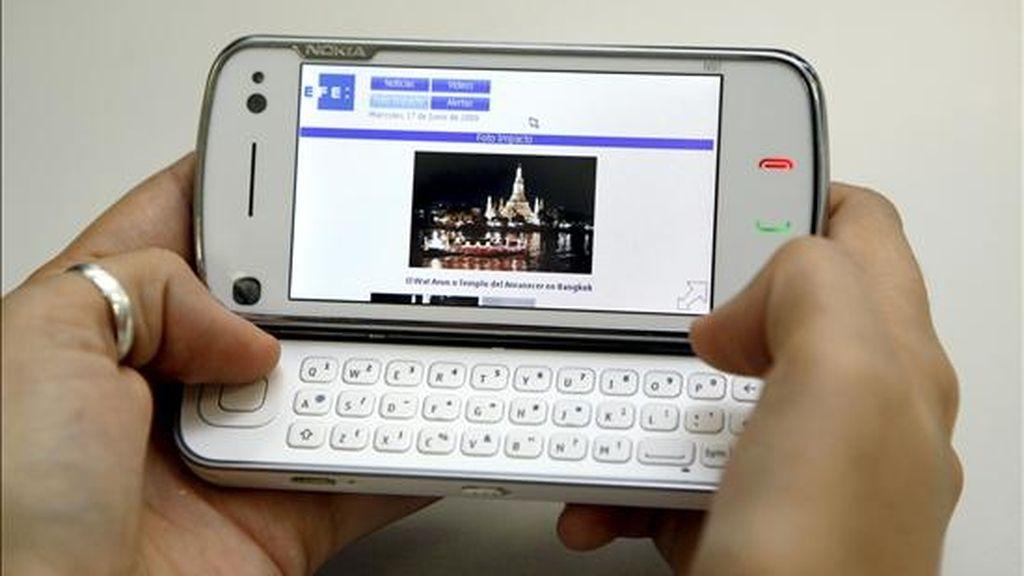 """Una persona maneja el móvil N97, definido por los directivos de Nokia como un """"ordenador real"""", que es un móvil en línea con las tendencias de tecnología táctil, pero que incluye un teclado completo que hace sencillo y rápido el uso de la mensajería. EFE"""
