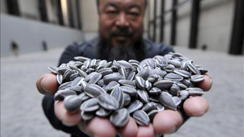 El renombrado artista chino Ai Weiwei sostiene un puñado de semillas de girasol de porcelana, durante la inauguración hoy de su exhibición 'Sunflower Seeds' en el Museo Tate Modern de Londres, Reino Unido. EFE