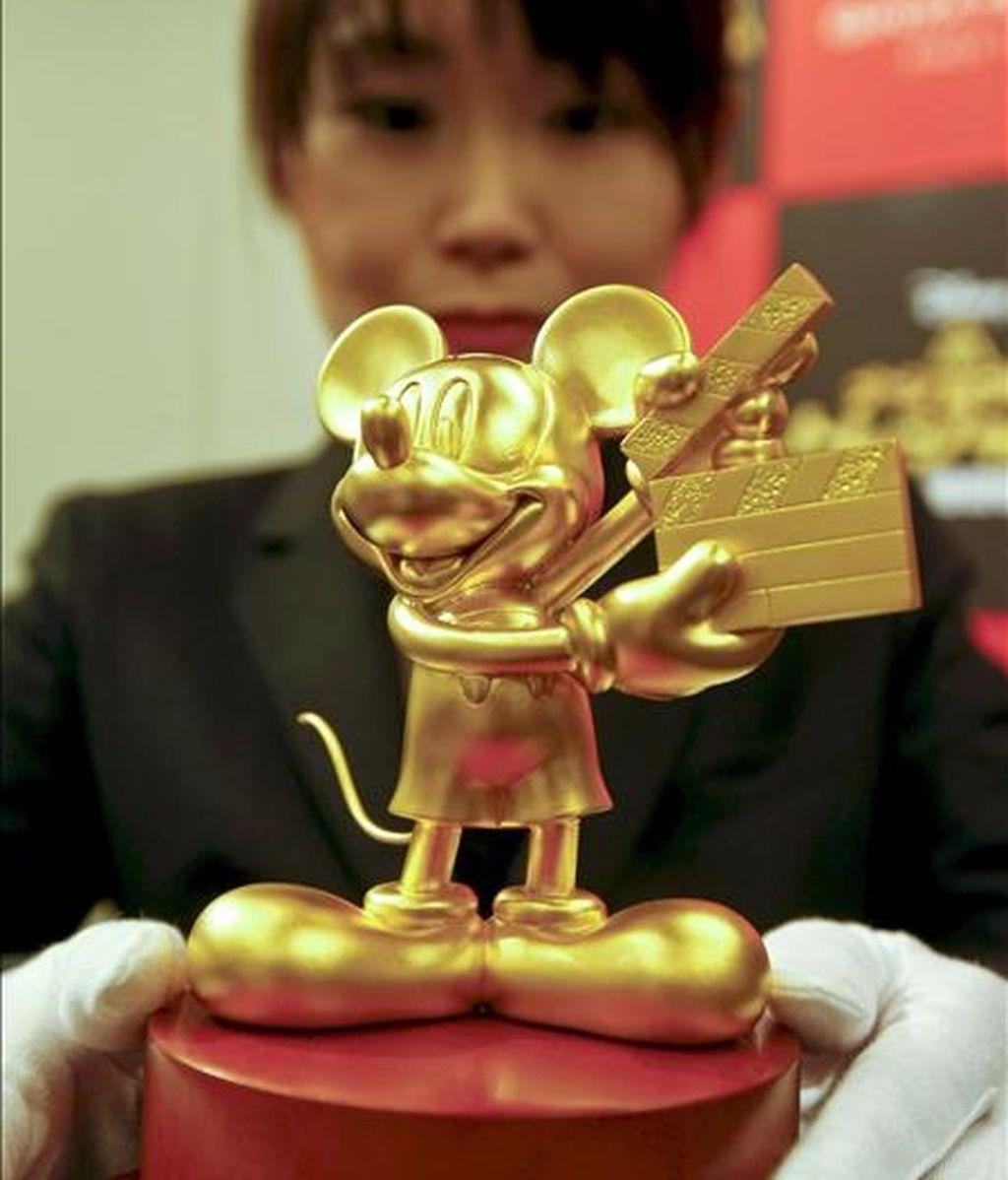 Una mujer coloca una figura de oro puro de Mickey Mouse en una rueda de prensa en Tokio (Japón). EFE/Archivo
