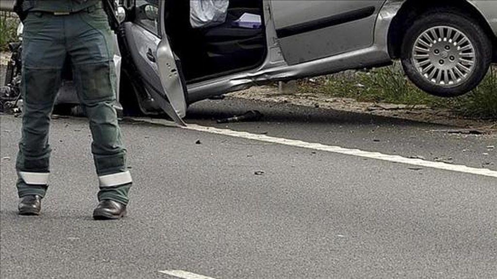 Un miembro de la Guardia Civil junto al vehículo implicado en un accidente. EFE/Archivo