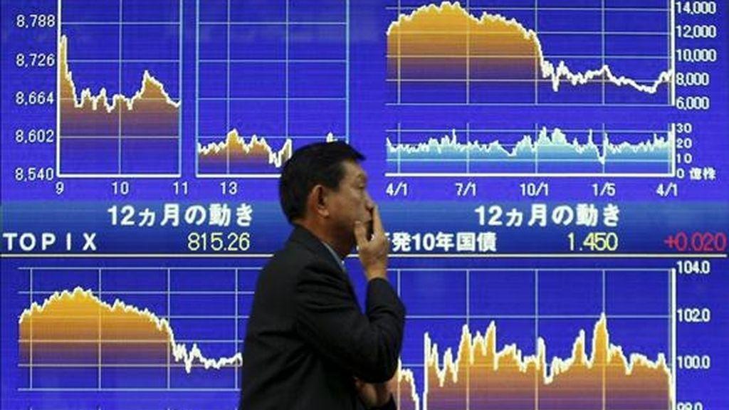 Un ejecutivo japonés camina frente a un tablero electrónico con valores de la Bolsa de Tokio (Japón). EFE/Archivo