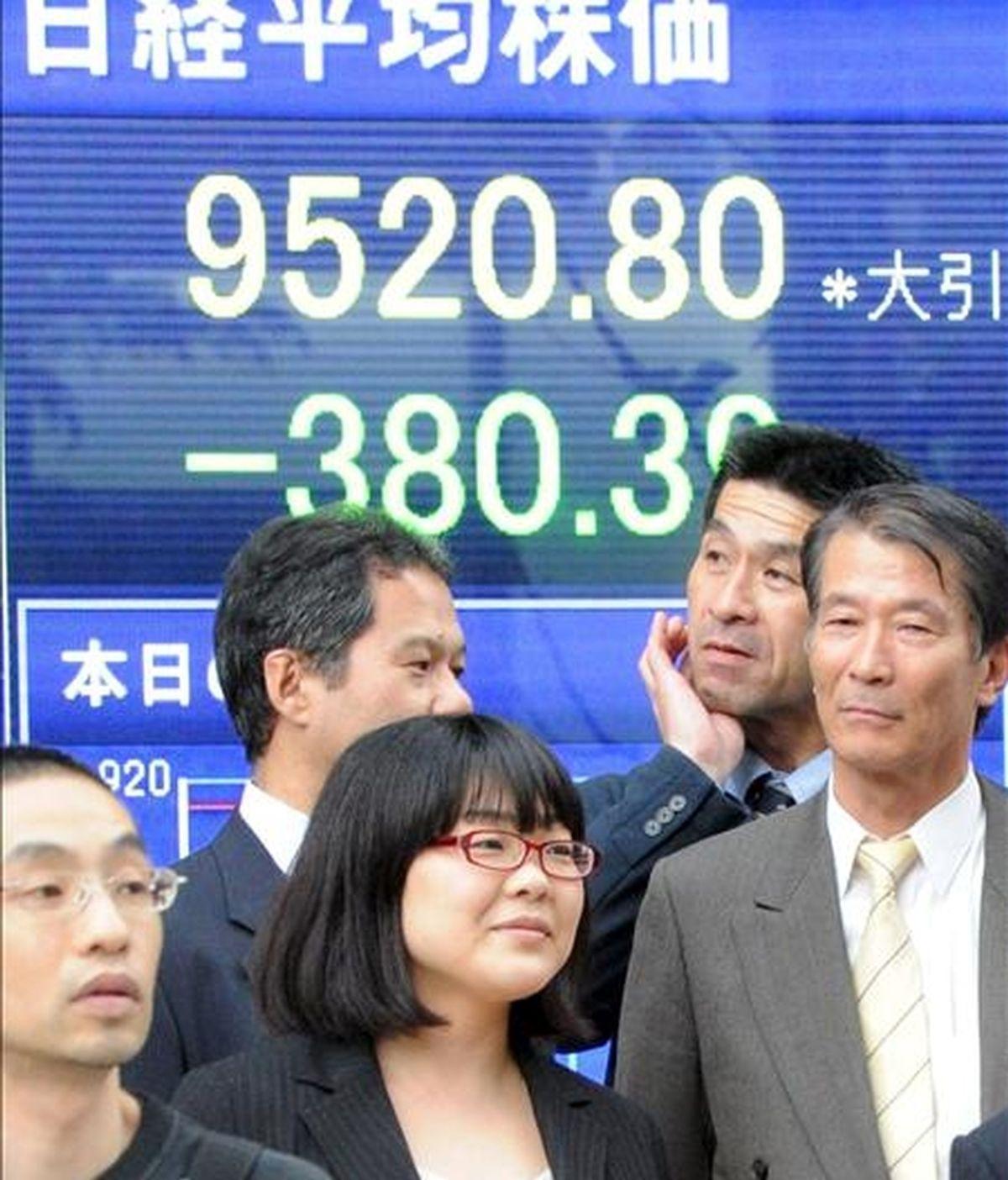 Ejecutivos japoneses caminan frente a un tablero electrónico con el valor de los índices de la Bolsa de Tokio. EFE/Archivo