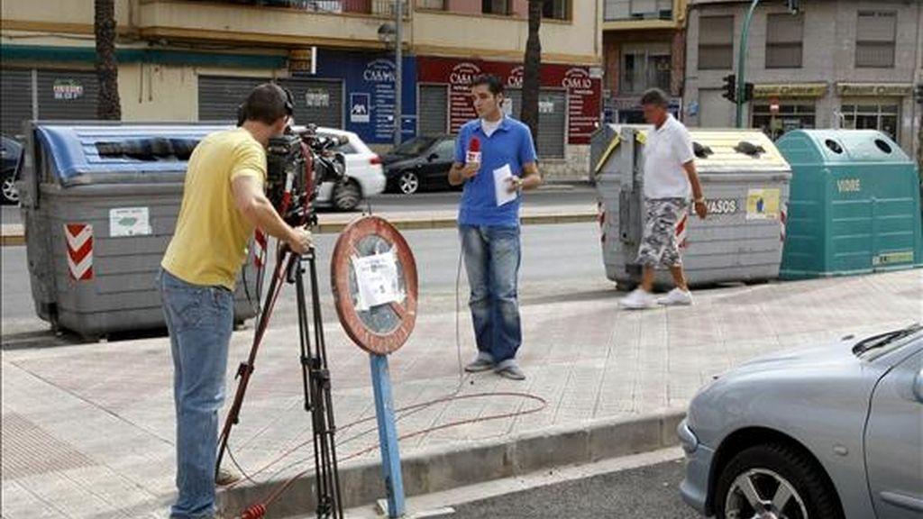 Un equipo de TV realiza un directo desde el lugar en el que se encontraba el contenedor en el que fue encontrada la mujer que ayer apareció descuartizada en una céntrica calle de la ciudad de Elche. EFE