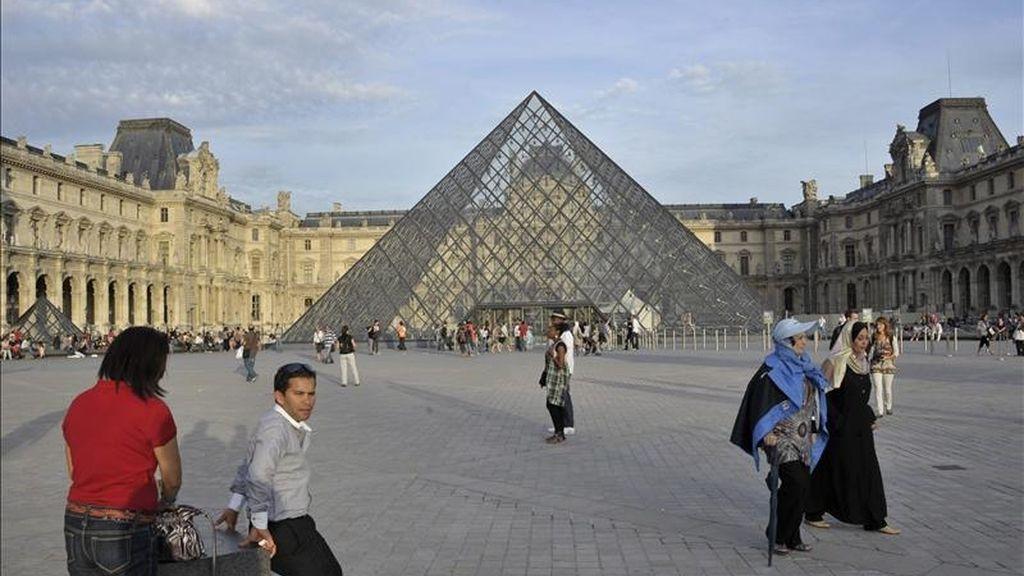 Paseantes caminan frente a la pirámide del Museo de Louvre. EFE/Archivo