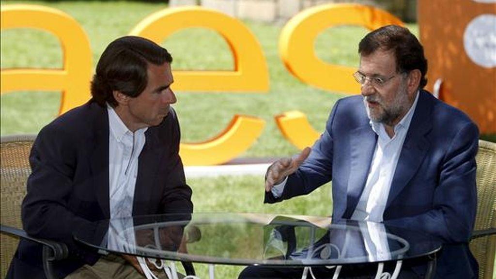 El presidente del Partido Popular, Mariano Rajoy (d), que intervino hoy en la clausura del campus de verano FAES, que tiene lugar en Navacerrada (Madrid), conversa con el ex presidente del Gobierno y el presidente de Honor del PP, José María Aznar. EFE