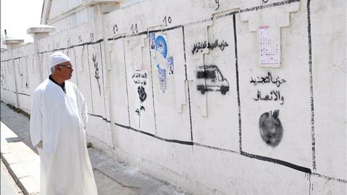 Un hombre camina junto a una pared pintada con símbolos de diferentes partidos de las elecciones locales de 12 de junio en Casablanca, Marruecos. EFE/Archivo