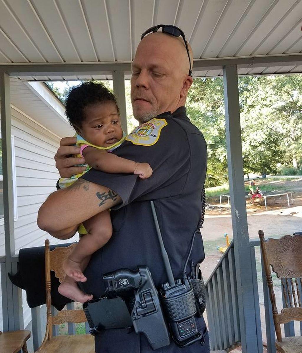 El agente Kenneth Knox y la bebé de dos meses a la que salvó la vida