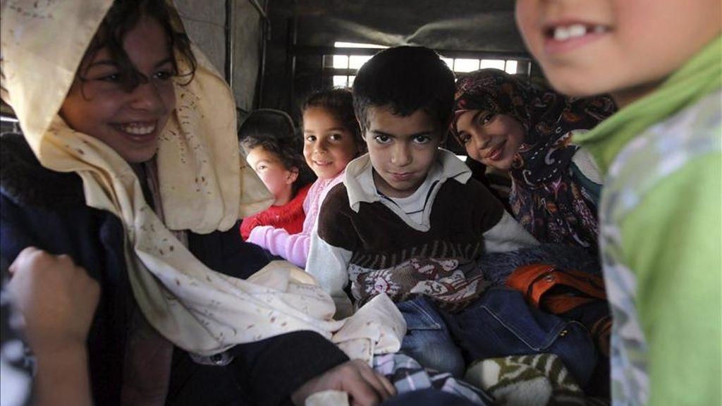 Una familia libia espera para cruzar la frontera hacia Túnez, en Wazin, sur de Libia. EFE