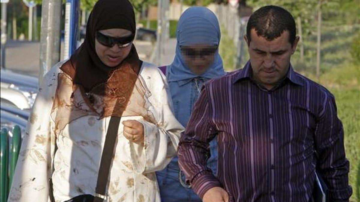 """Najwa Malha (detrás), la niña española de religión musulmana y origen marroquí que ha tenido que dejar su instituto en Pozuelo de Alarcón por asistir con el """"hiyab"""" islámico, llega esta mañana con sus padres a un centro cercano, el Gerardo Diego, que no le ha puesto ningún impedimento. EFE"""