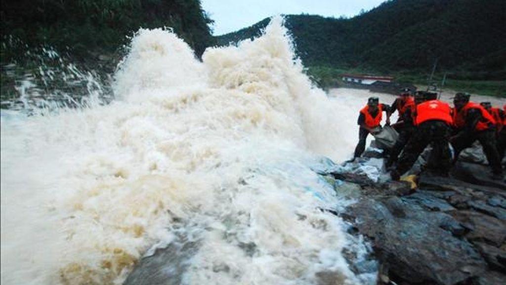 Fotografía disponible hoy, jueves 15 de julio de 2010, en la que aparecen varios policías lanzando rocas para reforzar la descarga del dique de Meixi Reservoir en el condado de Duchang, provincia china de Jiangxi. Inundaciones por las fuertes lluvias han ocasionado 118 muertes y 47 desaparecidos en lo que va corrido del mes en las provincias del sur del país. EFE