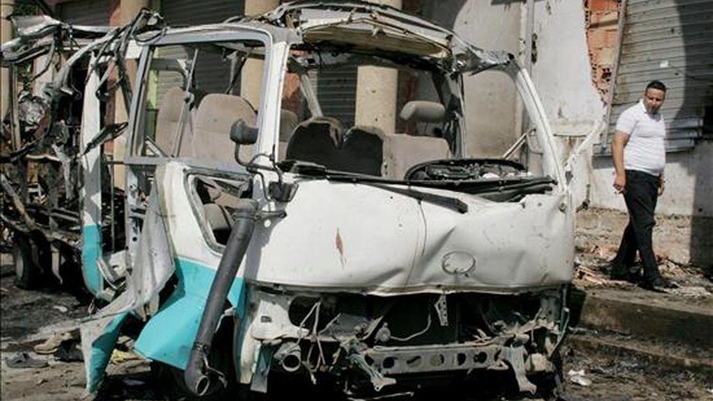 Un argelino pasa junto a un autobús destruido en un atentado suicida perpetrado en la ciudad de Bouira, a 120 km al este de Argelia, el pasado mes de agosto. EFE/Archivo