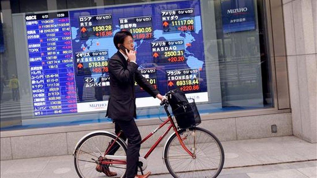 Un hombre de negocios japonés pasa junto a una pantalla que informa de varios valores bursátiles que cotizan en la Bolsa de Tokio . EFE/Archivo