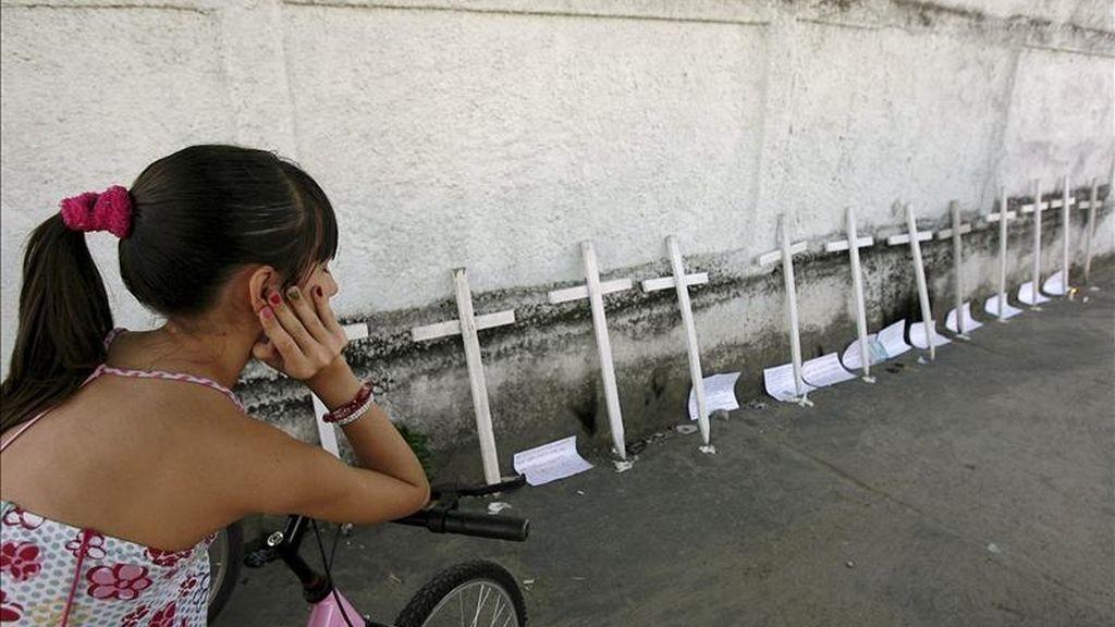 Una niña observa 12 cruces representando las víctimas de la masacre en la escuela Tasso da Silveira en Río de Janeiro (Brasil). La tragedia irrumpió en esa escuela este jueves cuando un exalumno mató a por lo menos doce niños e hirió a otros doce, antes de suicidarse. EFE