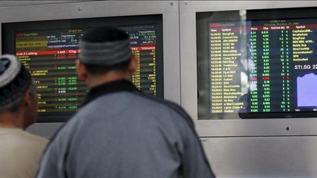 Dos inversores observan unos monitores en los que se muestran los valores de la Bolsa de Singapur. EFE/ARCHIVO