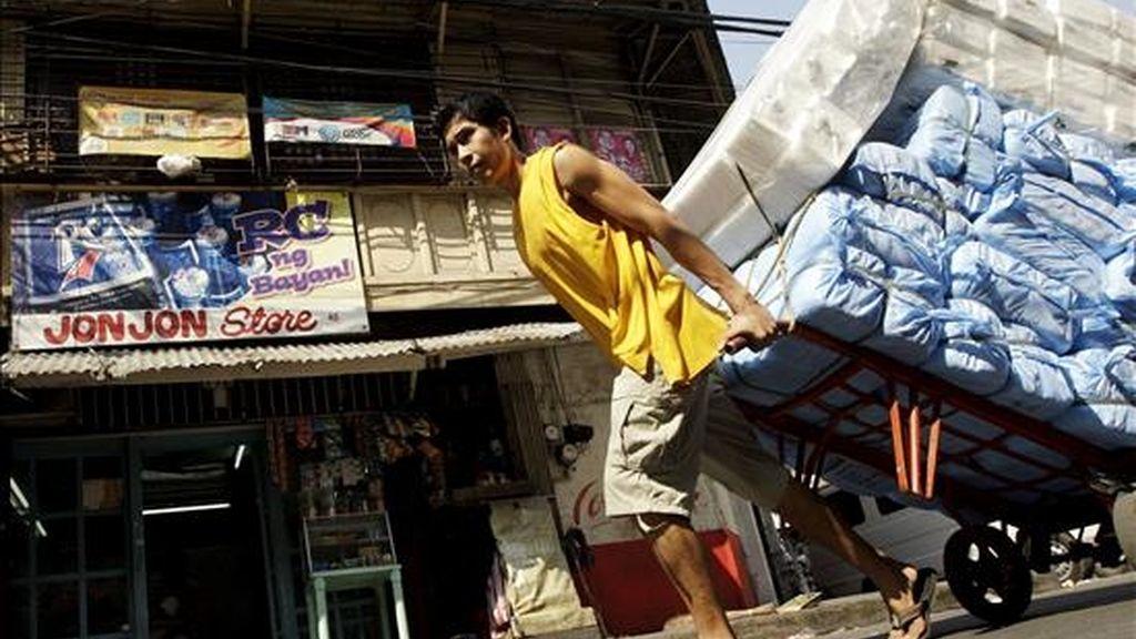 Un trabajador filipino tira de un carro lleno de mercancía en una calle de Manila, Filipinas. EFE/Archivo