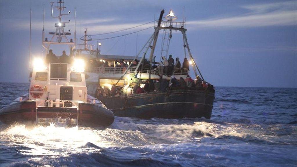 Guardias costeros ayudan a una embarcación recién llegada de Libia en Lampedusa (Italia) ayer domingo, 8 de mayo de 2011. EFE