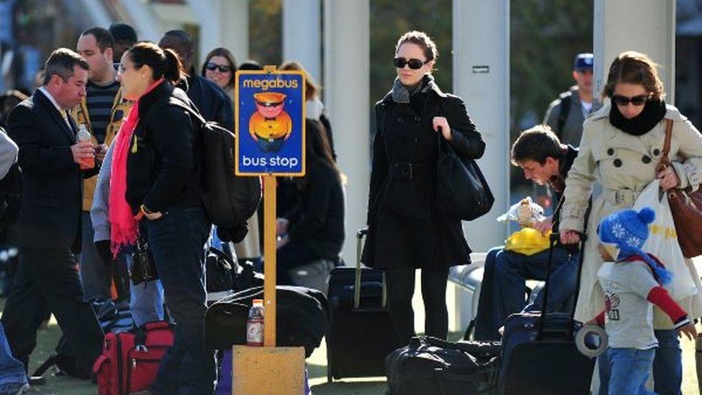 Viajeros esperan en la cola de un autobús