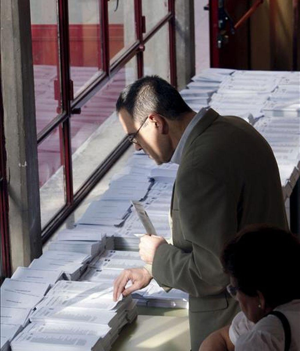 Un ciudadano elige las papeletas antes de ejercer su derecho al voto enlas elecciones al Parlamento Europeo, en el colegio Bernardette de Madrid. EFE/Archivo