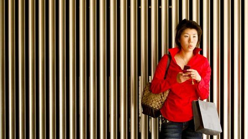 Una mujer observa su teléfono móvil en un edificio del centro de Tokio, Japón. EFE/Archivo