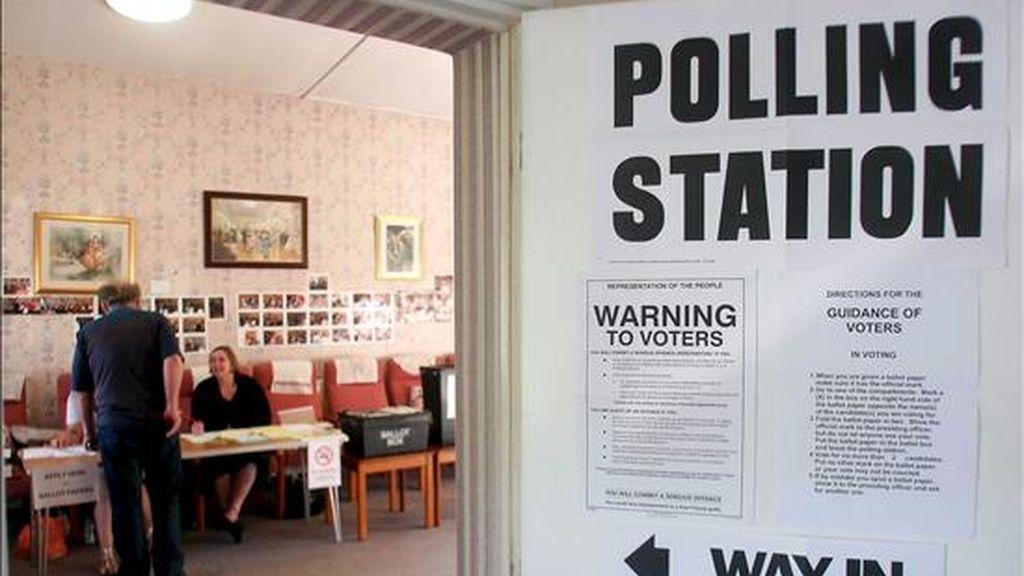 Varias personas son fotografiadas mientras depositan su voto para las elecciones europeas en Redditch, R. Unido, ayer 4 de junio. Hoy se celebran los comicios en Irlanda. EFE