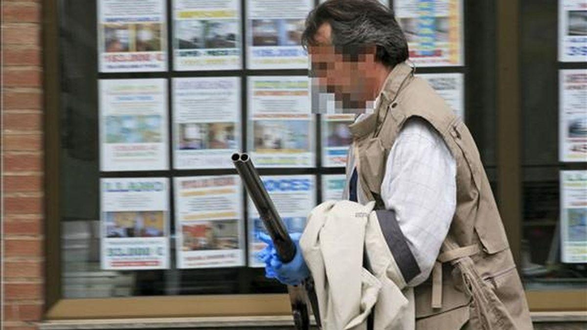 Un policía trasporta la escopeta de caza con la que una vecina de Gijón de 58 años ha sido asesinada hoy tras recibir dos disparos, al parecer tras mantener una discusión con su marido en el domicilio familiar de la calle Roncal, en el barrio gijonés de Pumarín. EFE