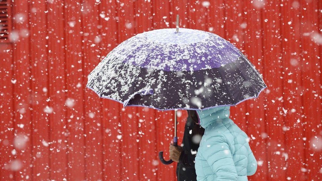 Varias personas caminan por una calle en la localidad cántabra de Reinosa, comunidad se encuentra en alerta por nevadas