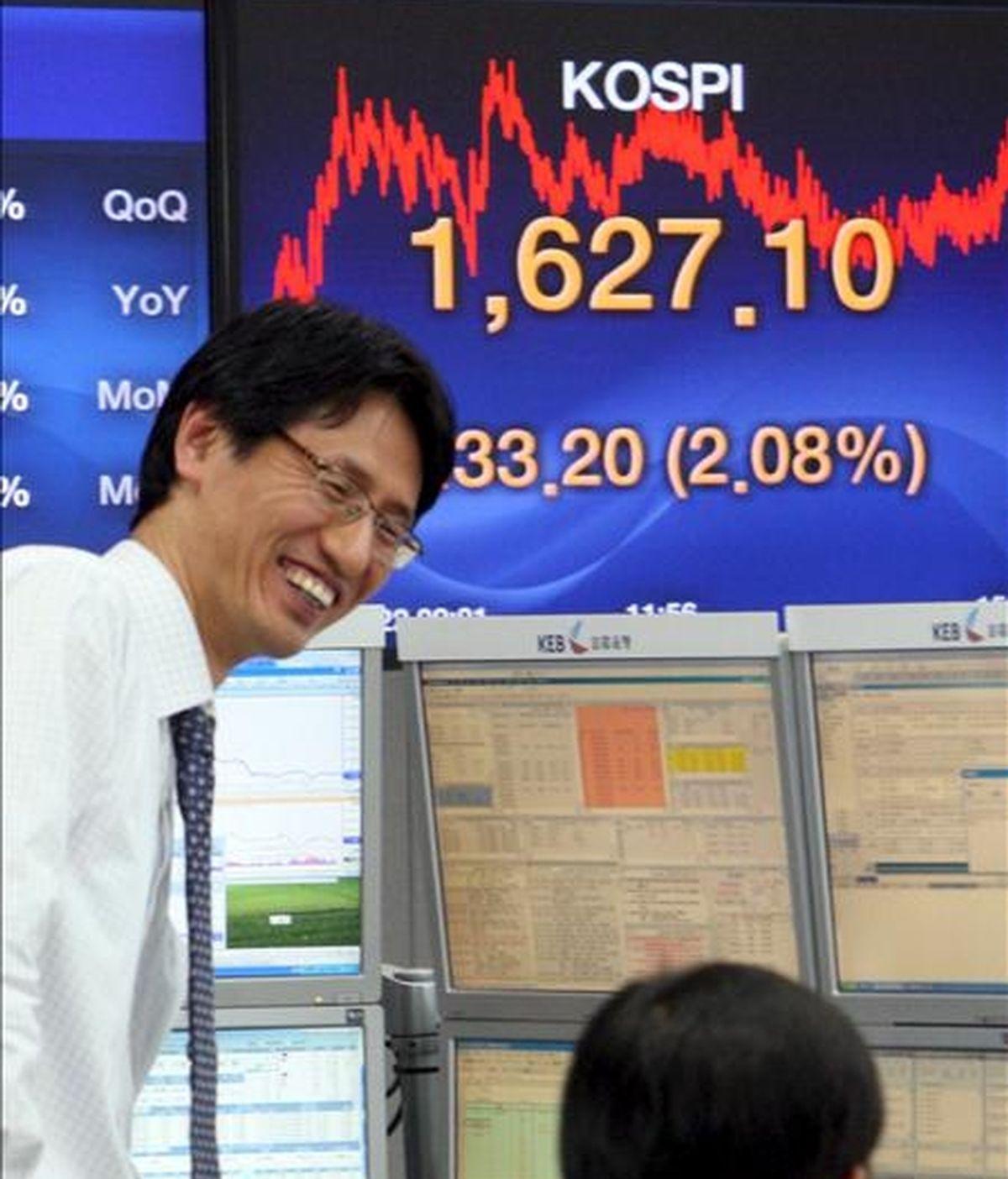 Dos hombres conversan frente a un tablero electrónico que muestra el valor del índice Kospi del mercado surcoreano. EFE/Archivo