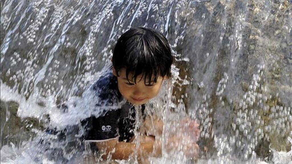Un niño juega con el agua en una fuente. EFE/Archivo