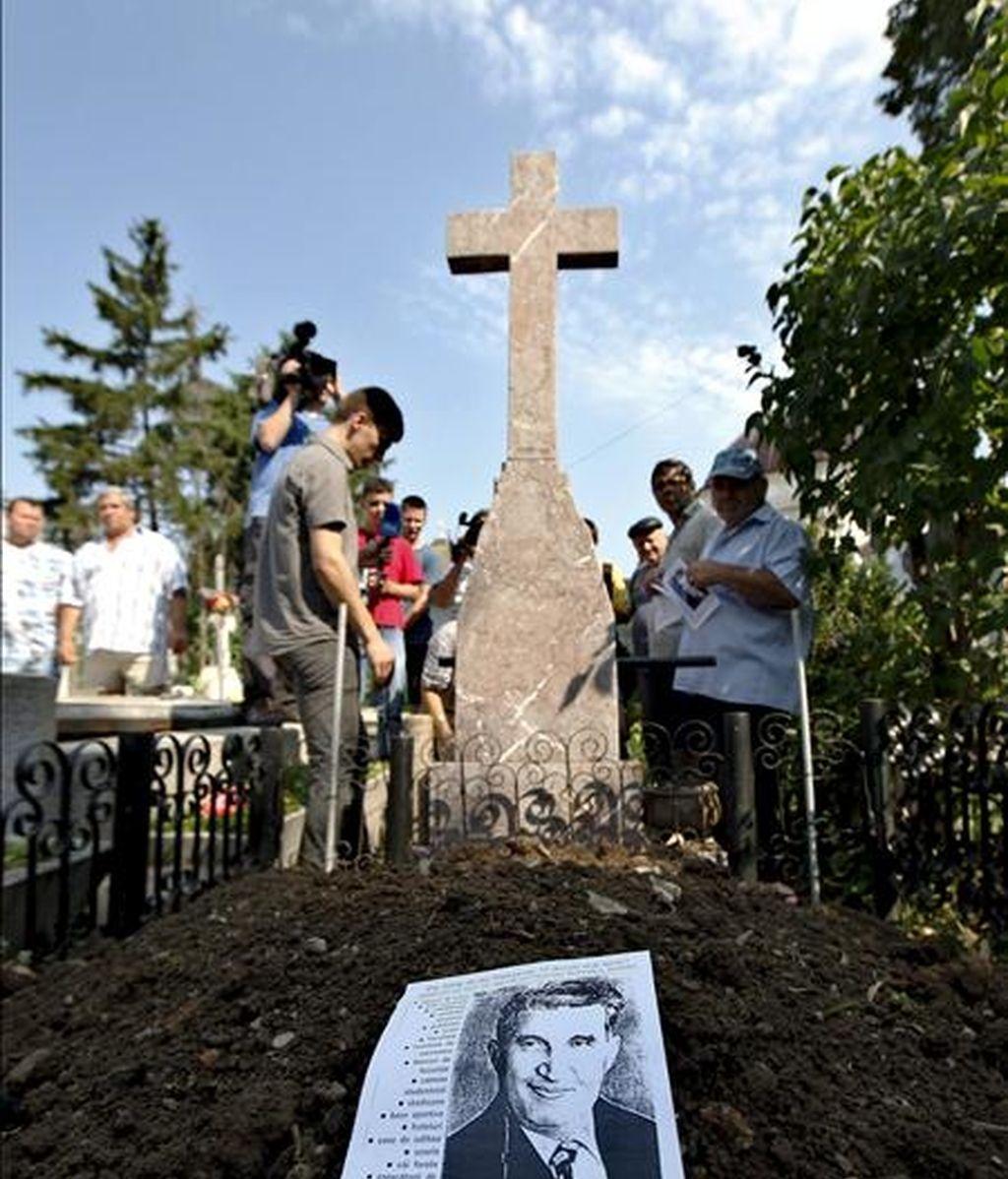Periodistas y seguidores de Nicolae Ceausescu congregados delante de la tumba del que fue dictador comunista rumano, tras su exhumación en el cementerio de Ghencea, en Bucarest, este miércoles. EFE