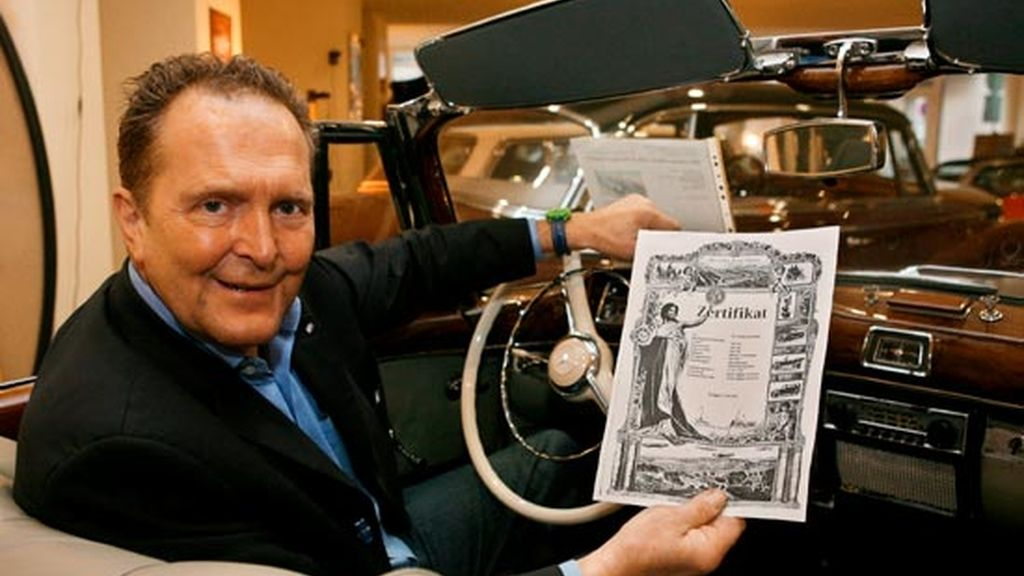 El anticuario de coches Michael Froelich posa con un certificado en un mercedes clásico en su tienda de Dusseldorf. Foto: EFE.