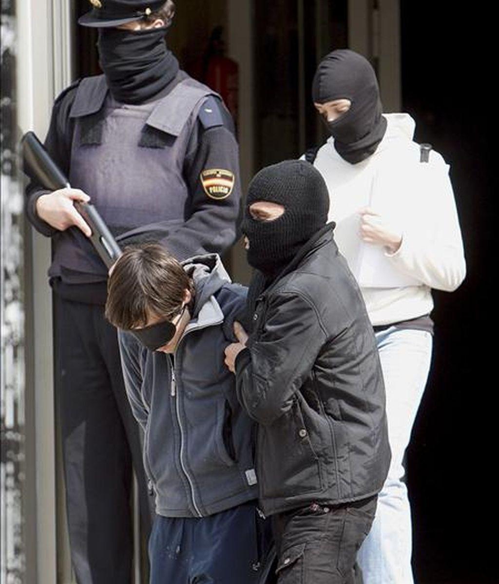 Agentes de la Policía Nacional trasladan desde la Subdelegación del Gobierno en San Sebastián a uno de las ocho personas (i) que han sido detenidas durante la madrugada en Hernani. EFE